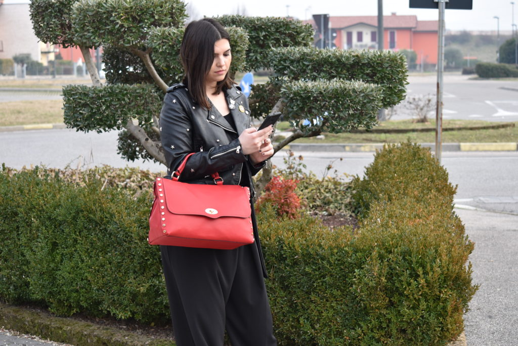 Giacca chiodo abbinata ad una borsa a mano rossa tipo postino con borchie di colore oro, pantalone a palazzo nero. Hand Bag 128 Rosso