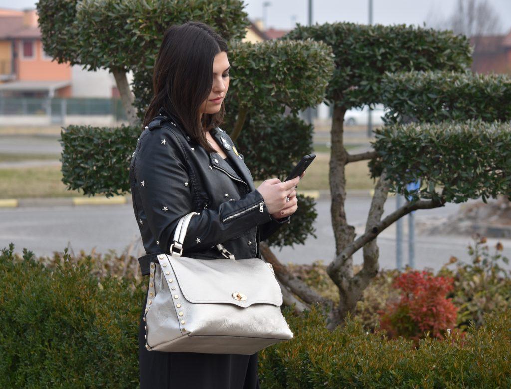 Giacca chiodo abbinata ad una borsa a mano argentata tipo postino con borchie, pantalone a palazzo nero. Hand Bag 128 Argento